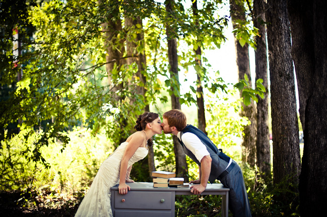 newlyweds kiss over desk in forest at Colonel Francis Beatty Park