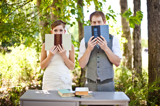 newlyweds holding old books to their faces