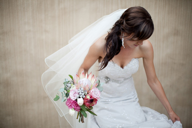 bride in veil holding protea flower bouquet