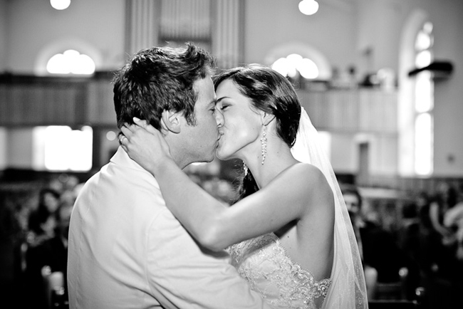 black and white photo of bride and groom kissing at alter