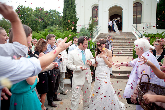 bride and groom walk down church steps as guests throw paper confetti