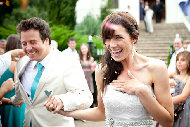 closeup photo of bride and groom with paper confetti flying all around