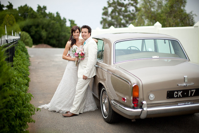 bride and groom lean against beige color vintage rolls royce
