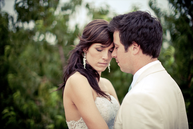 bride and groom with eyes closed embrace