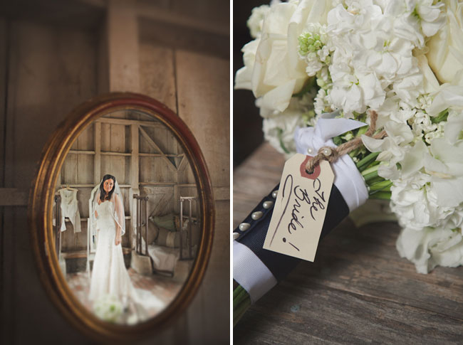 Mirror reflection of bride dressed in her gown standing in barn; white bridal bouquet