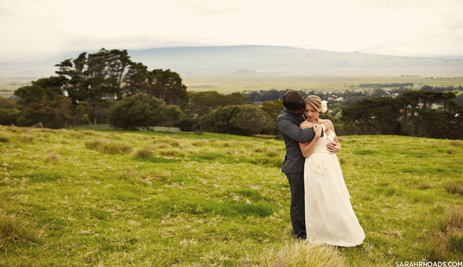 bride and groom embrace in field at Anna Ranch on Kona, Hawaii