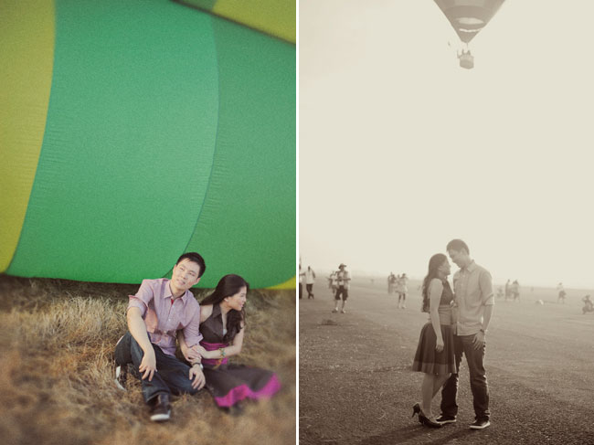 Couple sit on ground next to green hot air balloon
