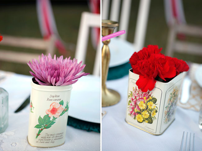 Tin cans with flower writing and flowers inside
