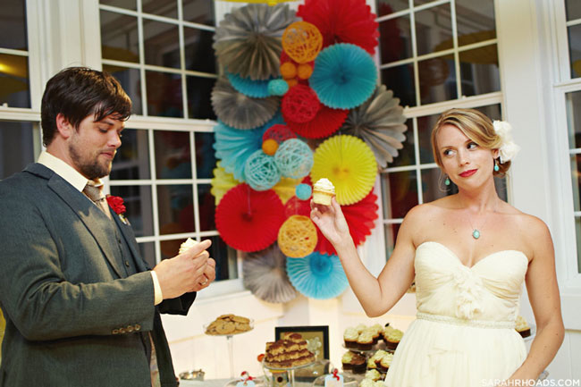 bride and groom eat cupcakes together