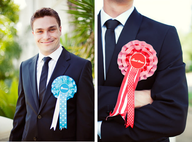 stylish south african wedding groom with blue ribbon rosette and groomsman with red rosette