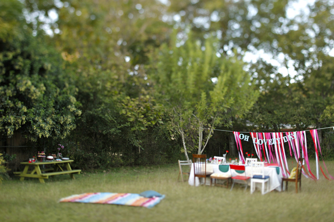 An outdoor styled brunch with ribbon backdrop that is full of color