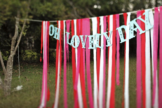 "red, white, and pink ribbon backdrop with the words, ""Oh lovely day"""