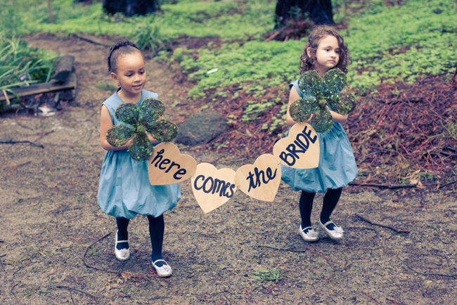 girls carry wood heart sign down aisle