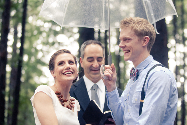 couple under umbrella for forest wedding ceremony