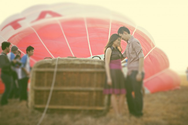 couple standing face-to-face next to hot air balloon basket on its side