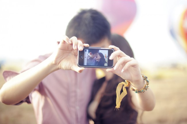 photo of couple taking a photo with their iphone