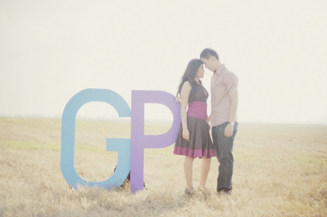 engagement session couple stand in field next to two giant letters G and P