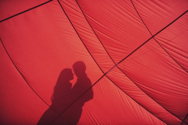 silhouette of couple behind red hot air balloon
