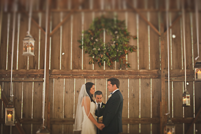 bride and groom hold hands at wedding ceremony in barn with officient in background