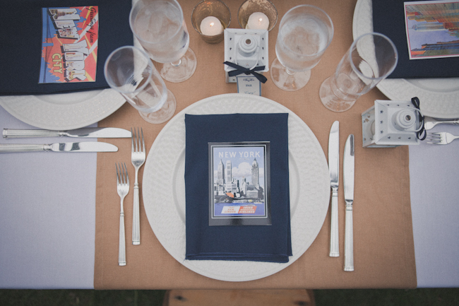overhead photo of travel inspiration wedding table setting with postcard on navy blue napkin