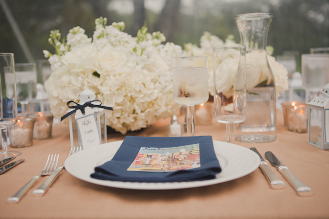 travel inspiration wedding table setting with postcard on navy blue napkin