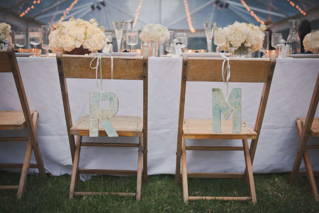 "Wood chairs at weddin reception with map monograms ""R"" and ""M"" attached to the bride and groom's chair"