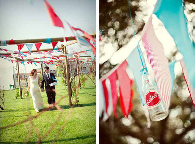 bride and groom walk under red white and blue pennants