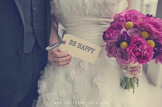 "Groom and bride with purple bridal bouquet an tag that says ""Be Happy"""
