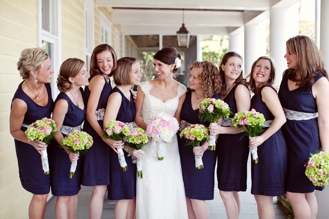 bridesmaids in matching navy blue dresses with lace sash belts