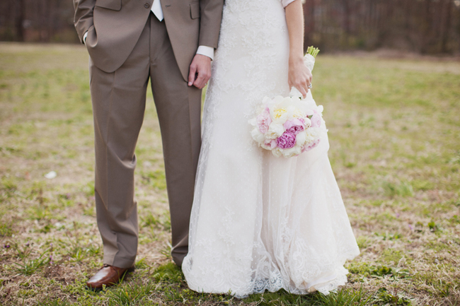 lower half of bride and groom standing on grass