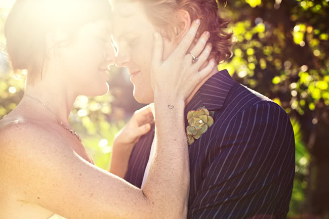 close up of bride and groom with eyes closed in sunlight