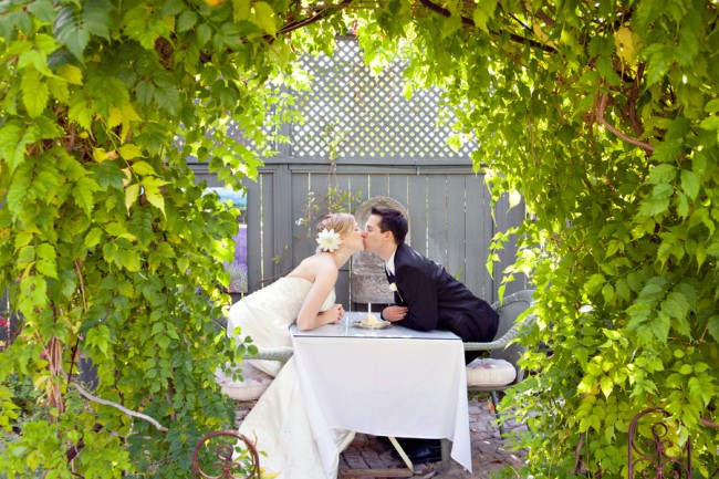 bride and groom kissing at table, framed by leaf foilage archway at The Lavender Inn