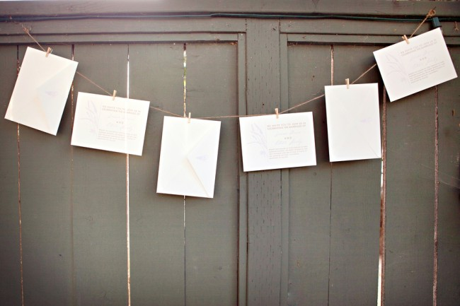 cards strung up against wood fence for lavender wedding