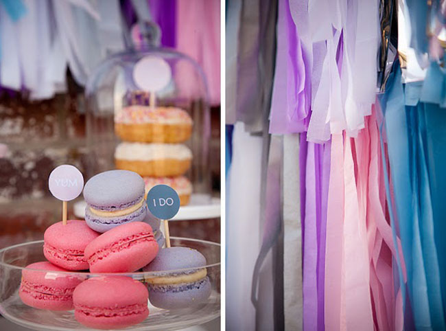 "pink and lavender macaroons with mini signs that say ""I DO"" and ""YUM""; colored pieces of fabric hanging"