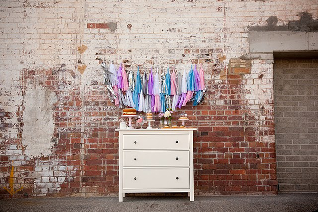 Cooking bridal shower set: white dresser with desserts ontop against a brick wall backdrop