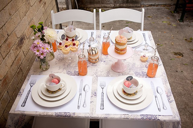 Table setting with cupcakes, donuts, orange drink, and macaroons in teacups