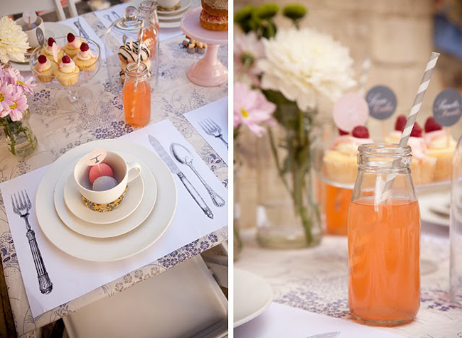 glass jar with orange drink and straw, macaroons inside teacup next to desserts