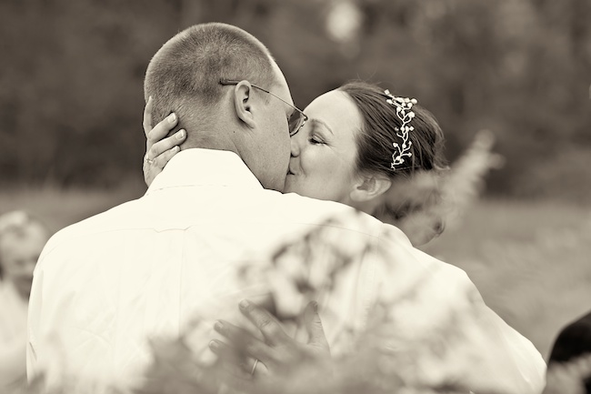Closeup black and white photo of bride and groom kissing at wedding ceremony at The Farm, Rome, Georgia
