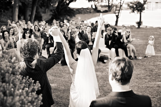 black and white photo of bride and groom raising arms just after ceremony
