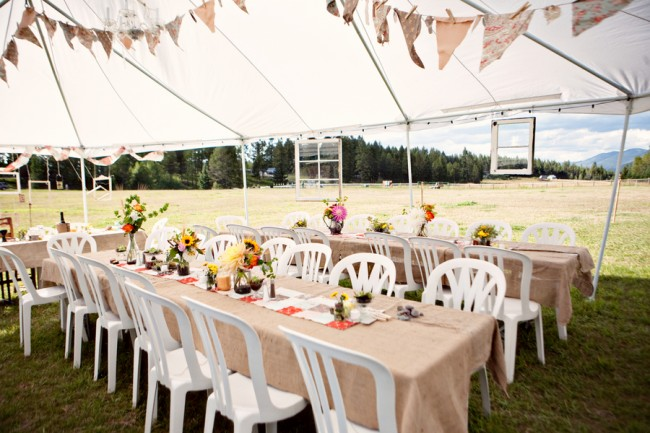 open canopy tent with reception tables and handmade bunting overhead