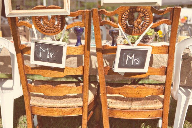 vintage chairs with a carved farm motif and chalkboard sign on back