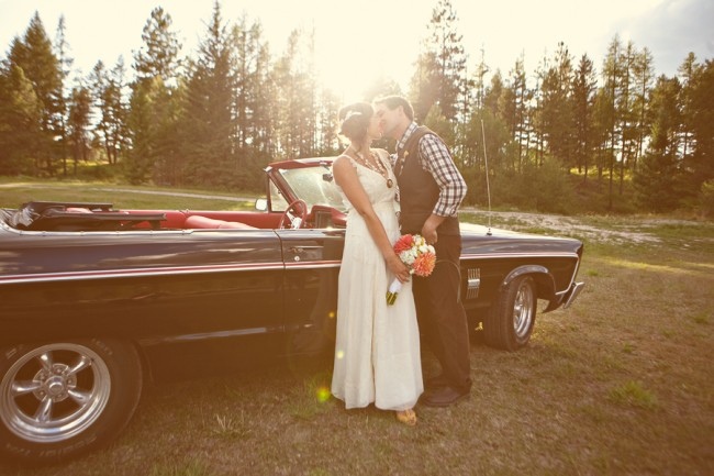 bride and groom kiss in front of vintage black convertable car