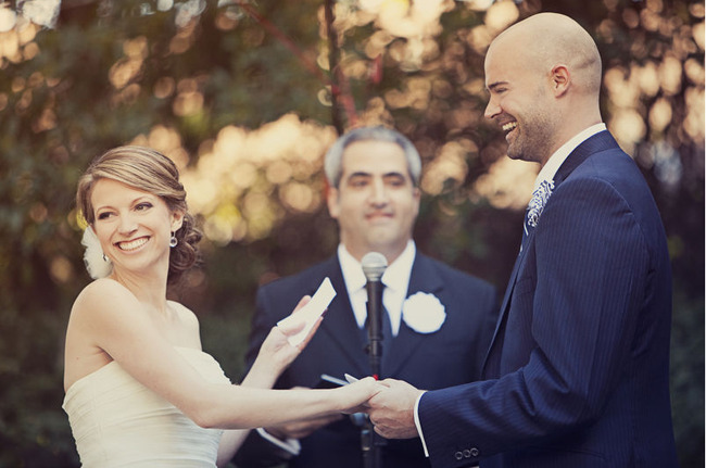 Bride and groom smile while reading vows