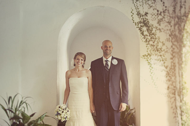bride and groom stand in white arch doorway at Governor Thomas Bennett House