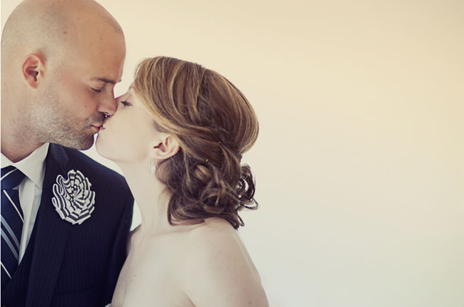 bride and groom kiss against white wall