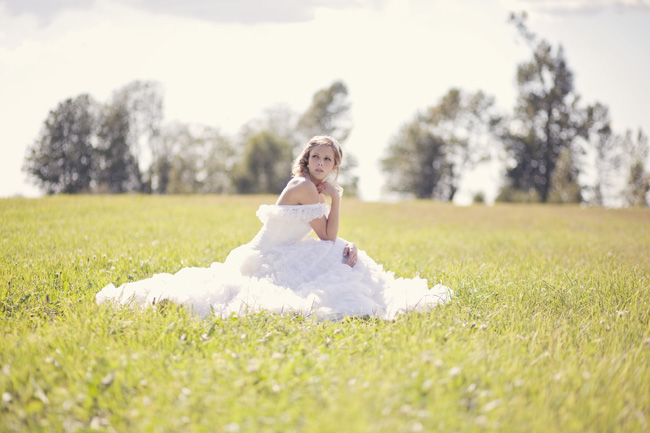 bride siting in field grass