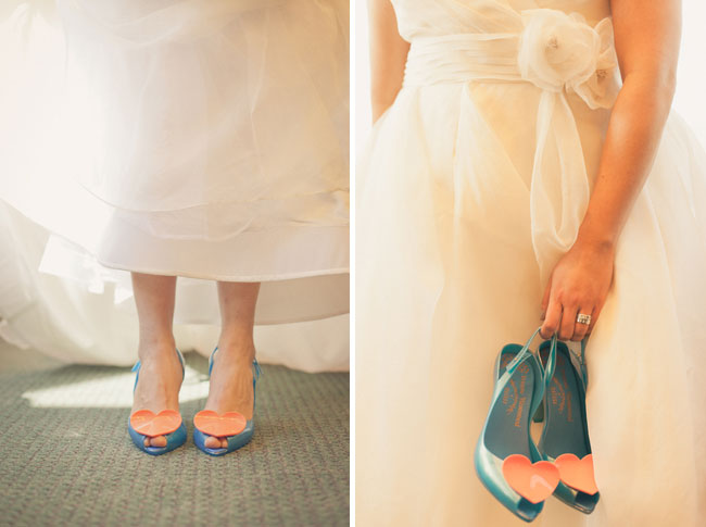 bride holding her blue wedding shoes with big hearts on the toe