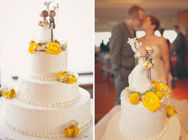 Three-tiered wedding cake in white with yellow flowers addorning; unique personalized cake topper