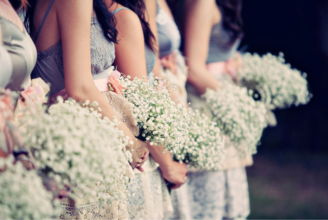 Bridesmaid in a row holding baby's breath bouquets