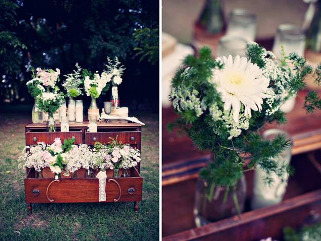 vintage dresser at outdoor wedding filled with baby's breath bouquets in mason jars